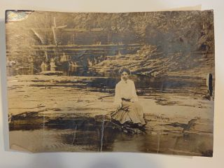 Silver print photograph of a woman seated on a river bank (ca. 1910). Silver print photograph